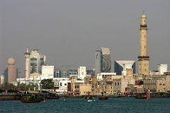 Dubai Creek, the historic focal point of life in the city, is a natural seawater inlet that cuts through the city's centre and separates Deira from Bur Dubai. The creek is alive with trade and tradition, the loading and unloading of trade ships that still travel ancient routes, and the beautiful promenades that line both sides of the water. In this view from near the mouth, the Grand Mosque dominates the Bur Dubai skyline, while the buildings of Deira are behind, including the Etisalat building with the golf ball on top, the Dubai Creek Tower, the curved National Bank of Dubai, and finally the triangular Dubai Chamber of Commerce building.